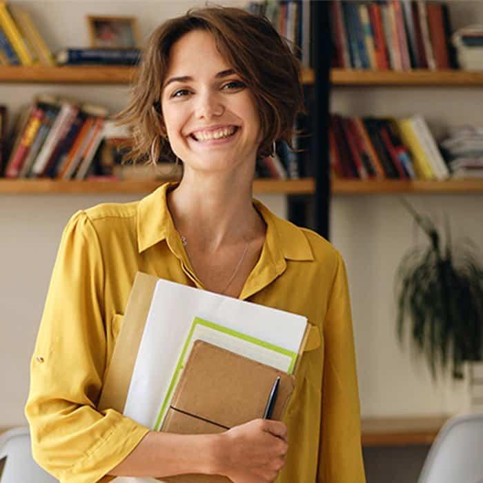 mujer sonriente con cuadernos en el brazo